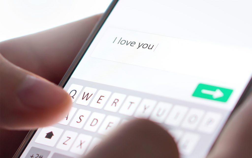 """Roamnce-Scammer schreibt auf dem Smartphone """"I love You"""""""