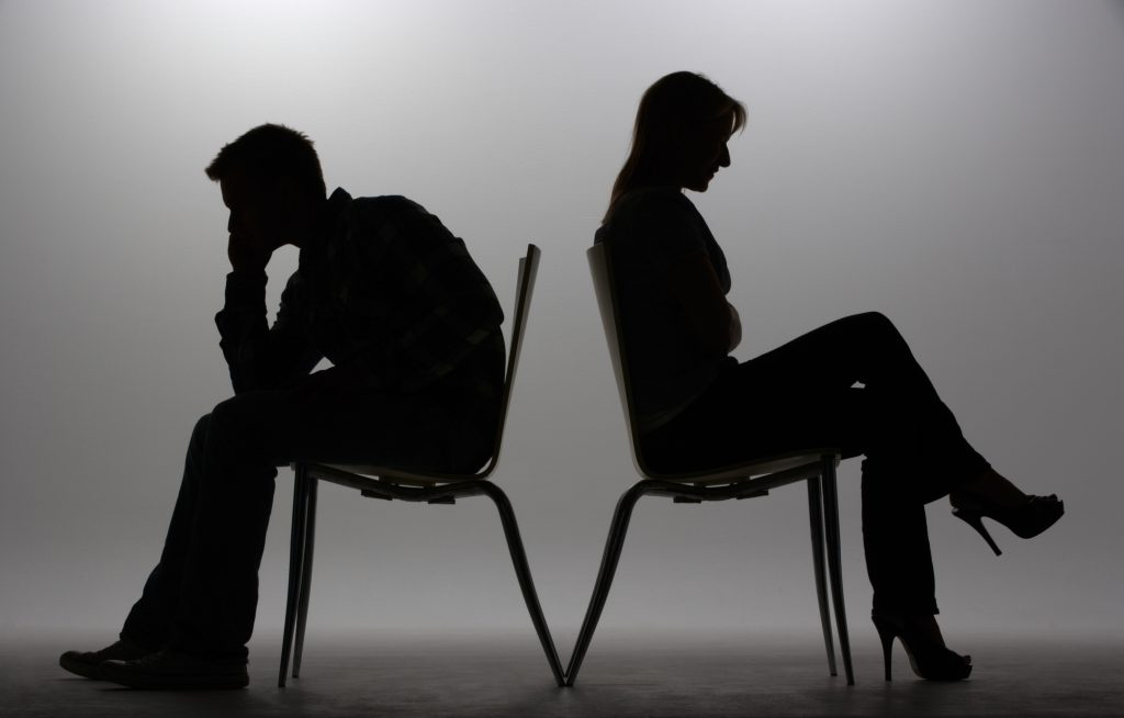 Silhouette eines Mannes und einer Frau, Rücken an Rücken auf Stühlen sitzend