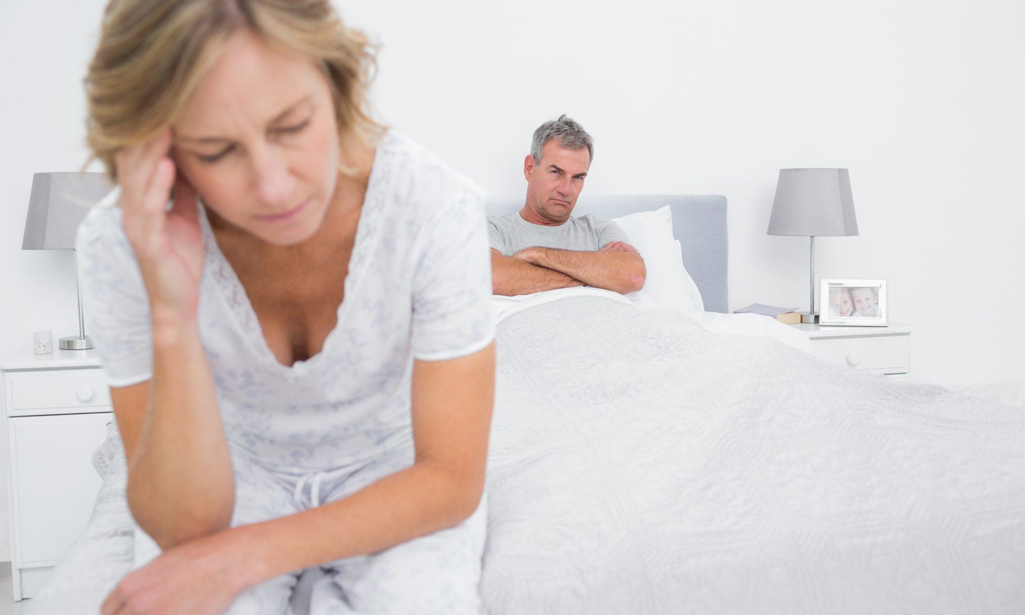 Unglückliches Paar sitzt nachdenklich im Bett