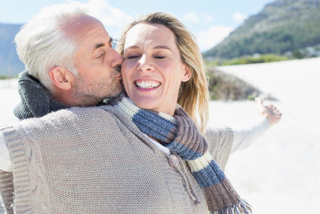 Paar steht am Strand in warmer Kleidung, glücklich und sorgenfrei