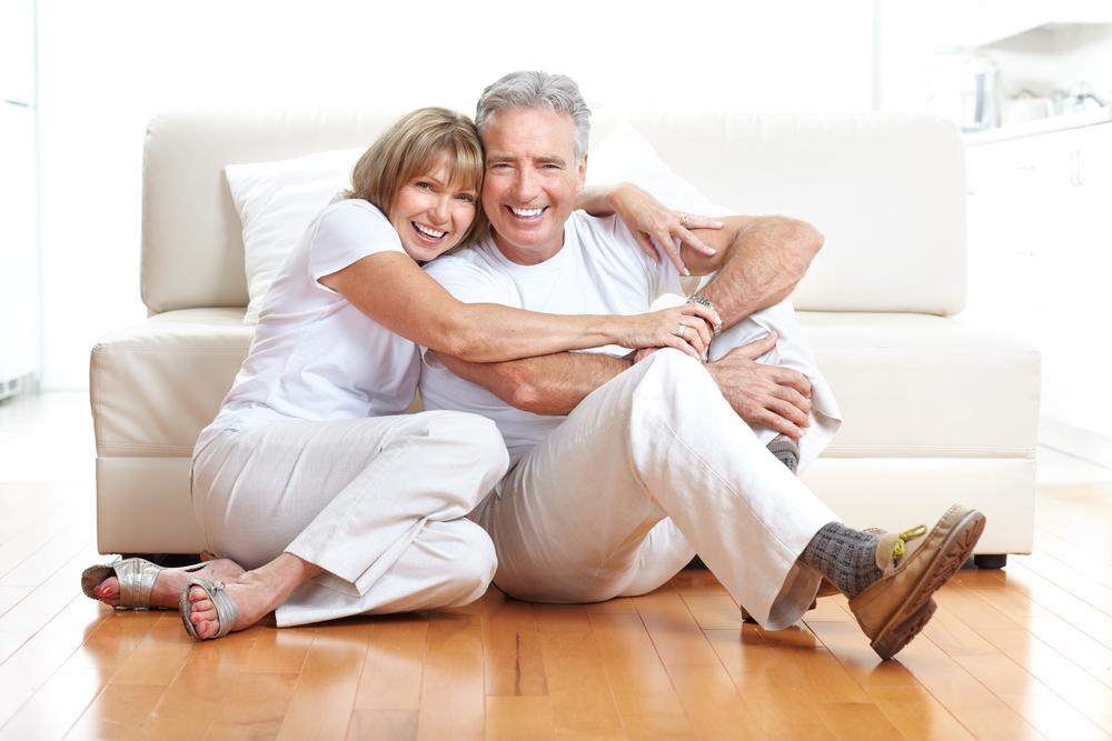 Reifes Paar sitz fröhlich umarmend auf dem Boden vor einer Couch