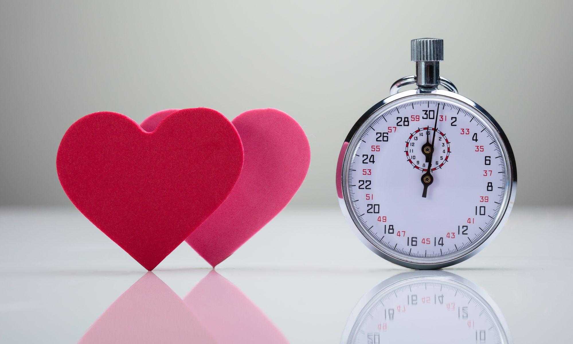 Zwei rote Herzen mit einer Stoppuhr - Speed-Dating