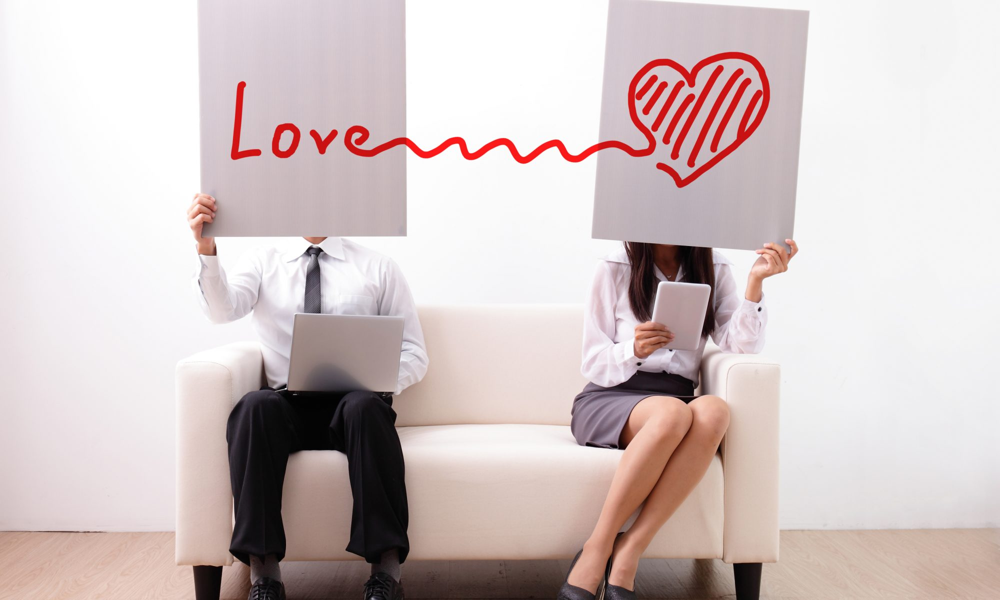 Frau und Mann halten Schilder vor das Gesicht mit Herz und Love