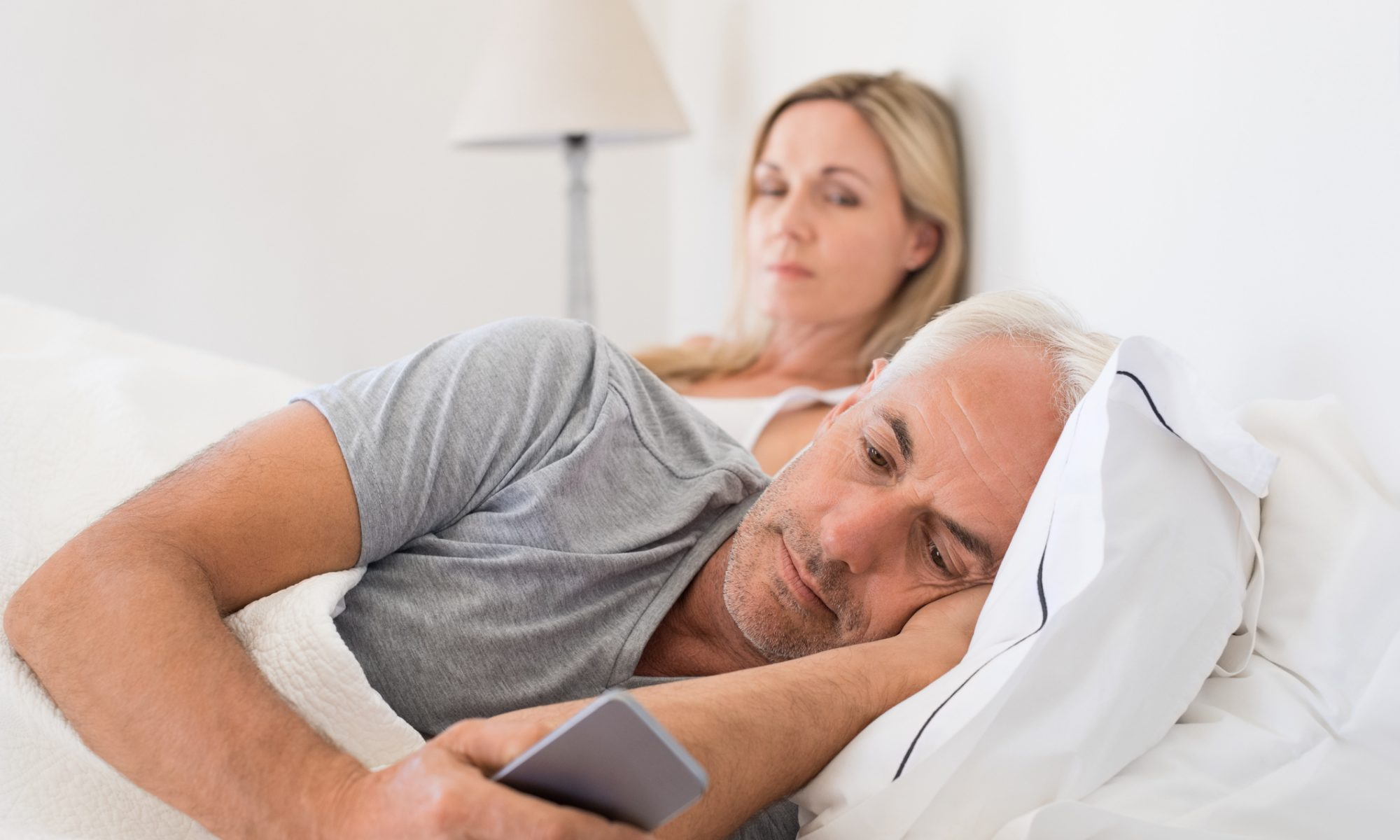 Eifersüchtige Frau beobachtet ihren Mann am Handy