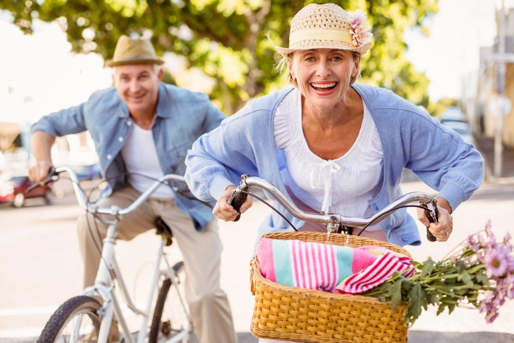 Älteres Paar fröhlich mit dem Fahrrad unterwegs