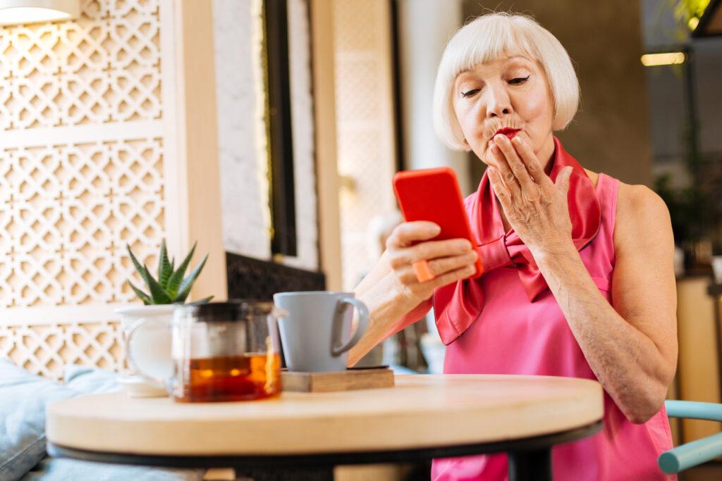 Ältere dame macht einen Video Anruf und schickt einen Handkuss