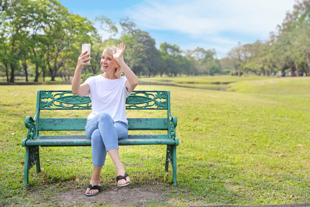 Frau mittleren Alters sitzt im Park und macht einen Viedeo call