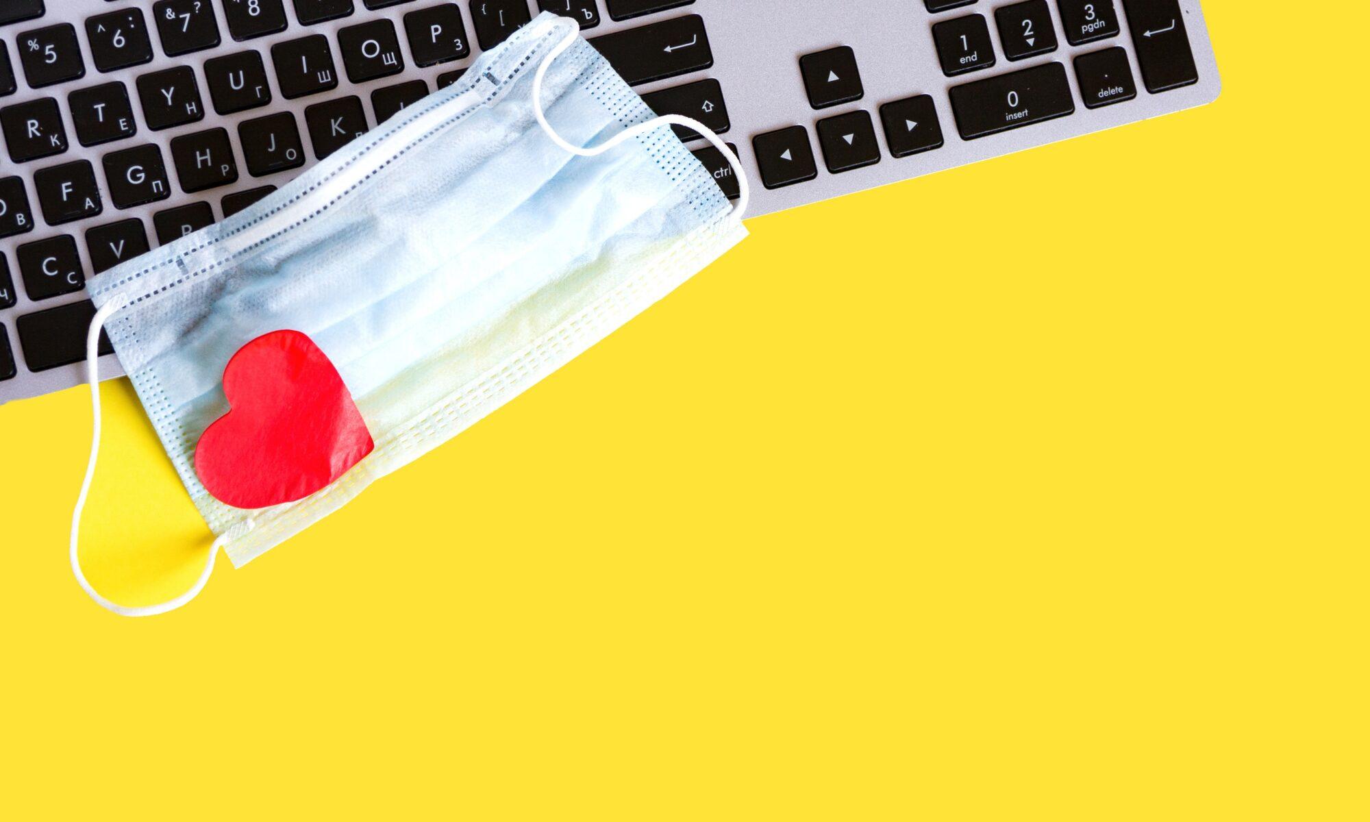 Gesichtsmaske und Herz liegen auf einer Tastatur