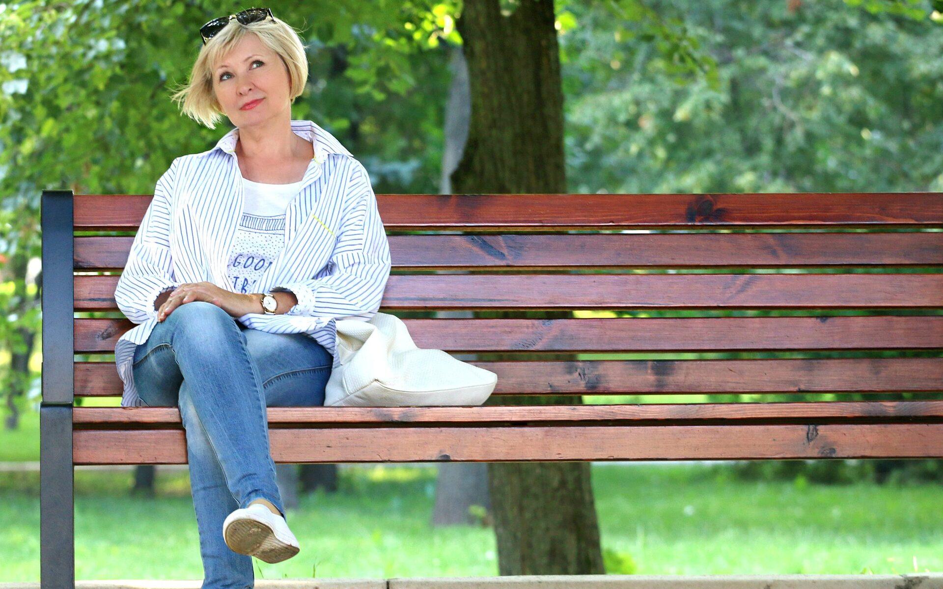 Frau sitzt alleine auf einer Bank