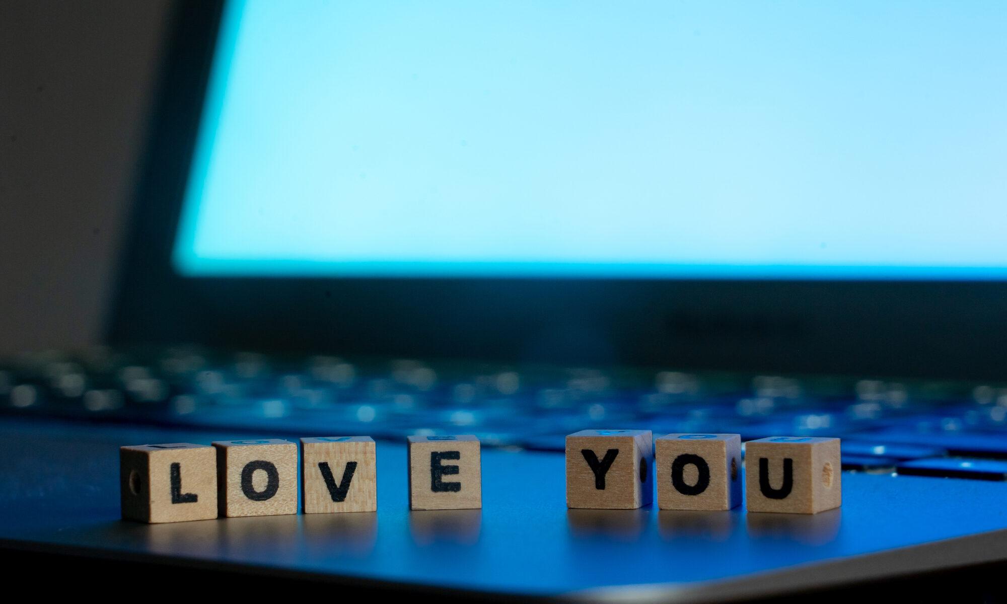 """Schriftzug """"Love you"""" vor Laptop"""