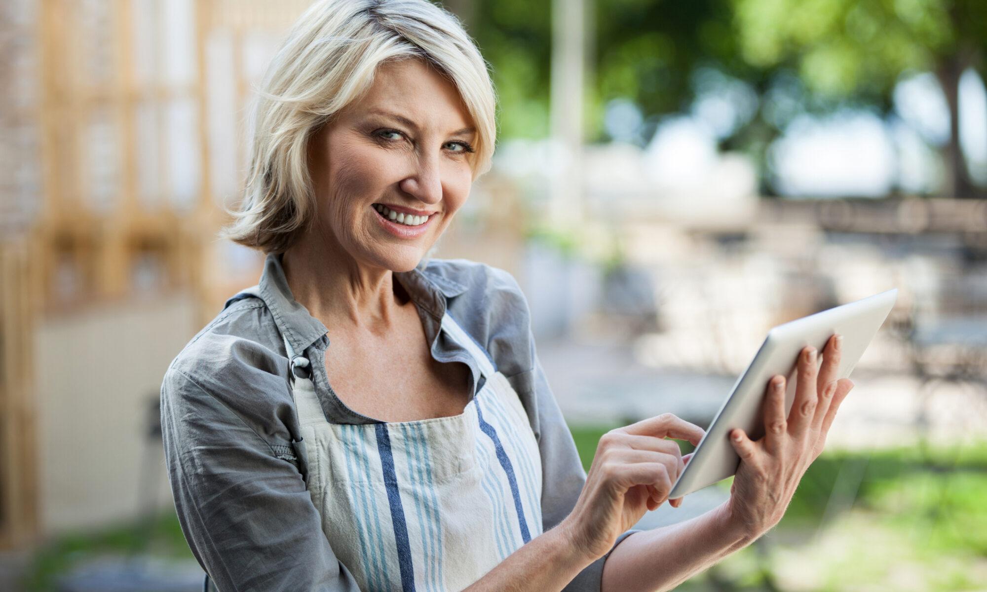 Ältere Dame mit Tablet beim online dating